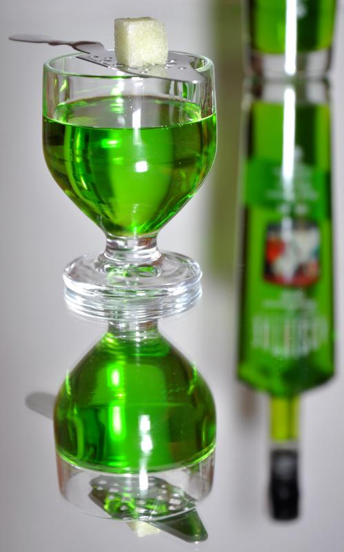 A small glass of absinthe with a sugar cube and absinthe spoon.