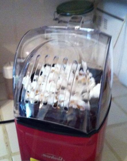 An air-based popcorn popper uses a steady flow of hot air to heat kernels to the point of popping.