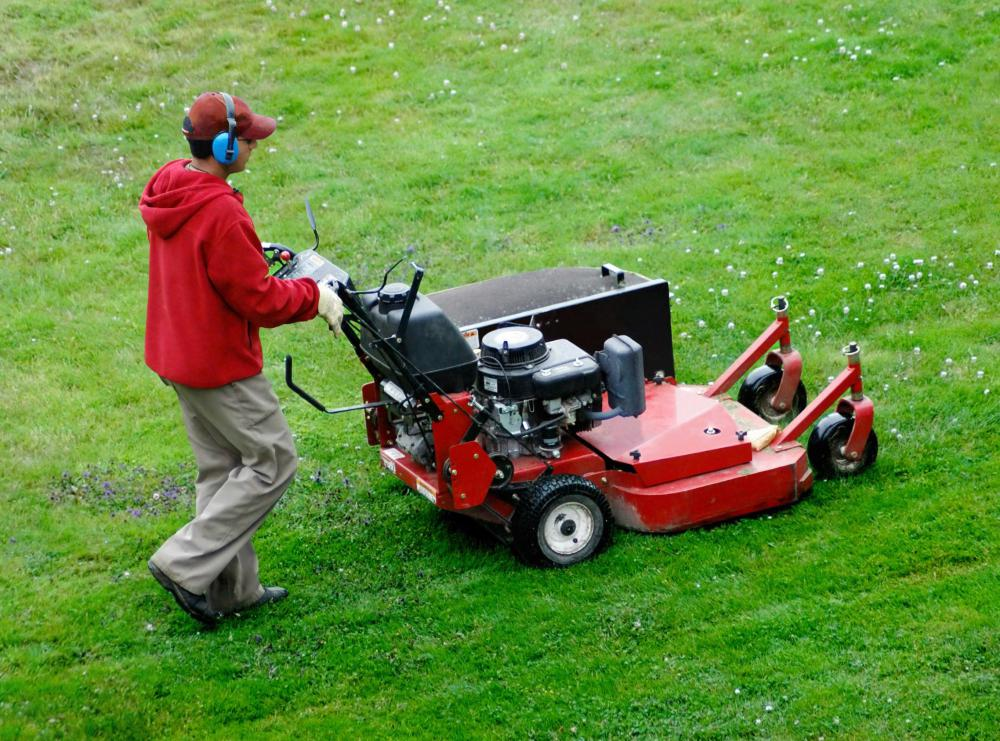 A man using a lawn mower.