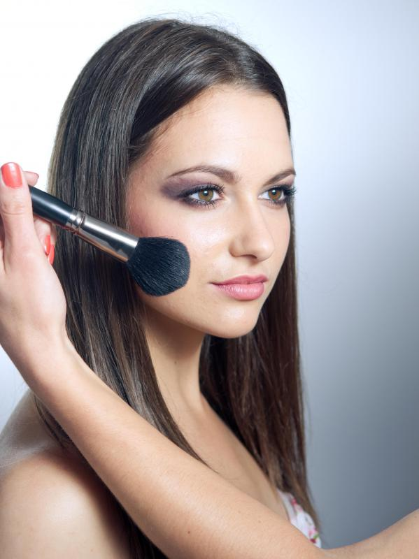 A woman has makeup applied to her face with a blush brush.