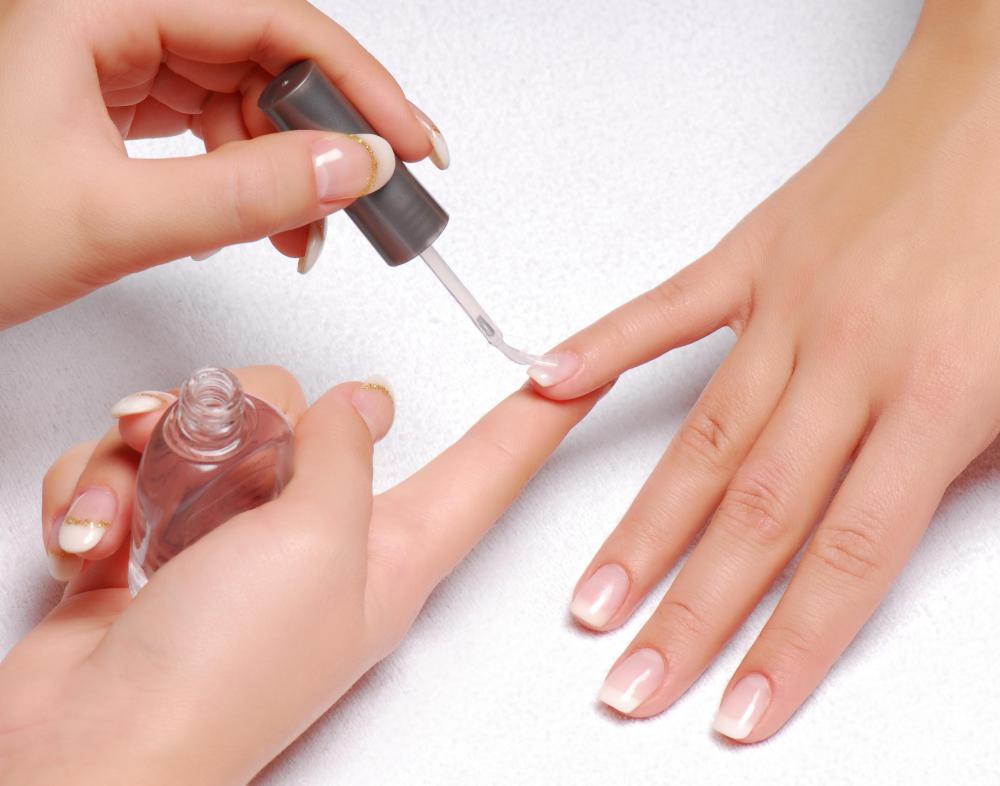 A nail technician applying clear nail lacquer to a woman's fingernails.