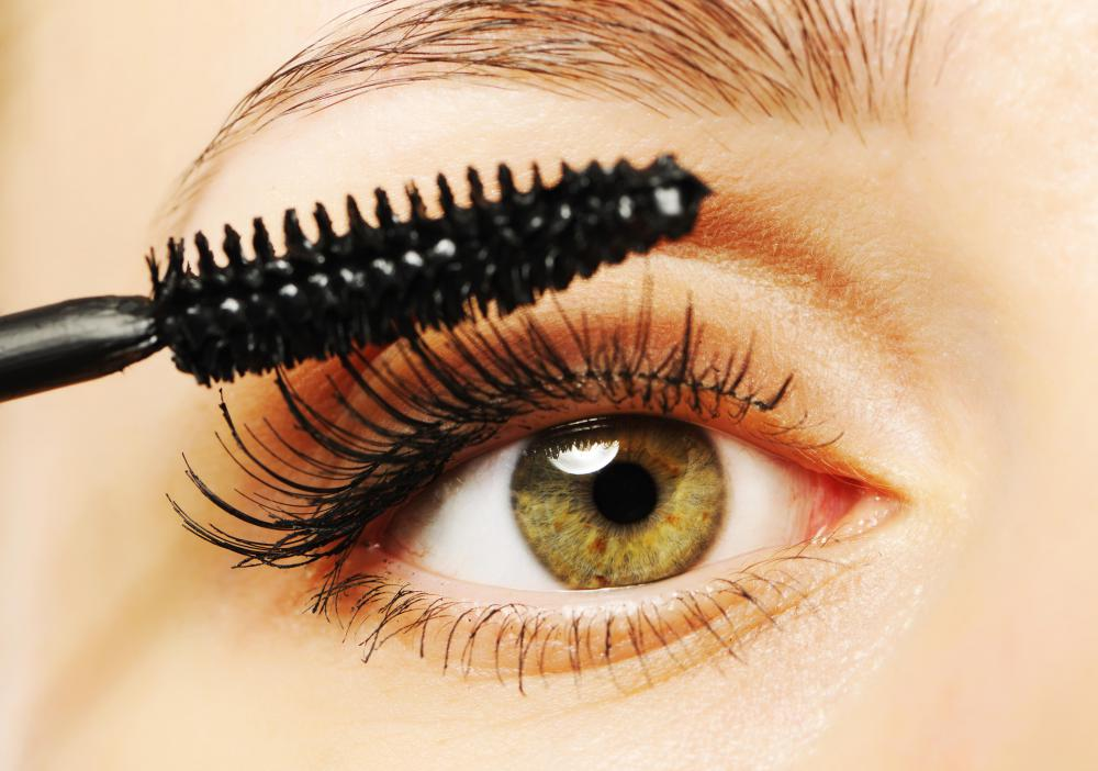A woman applying mascara, a type of cosmetic.