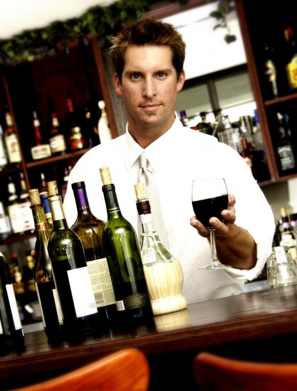 Bartender serving a glass of wine in a vintage glass.