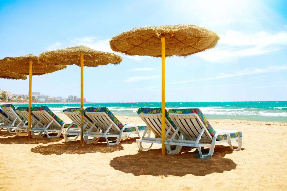 Some beach chairs may have an umbrella attached to help protect people from the sun.
