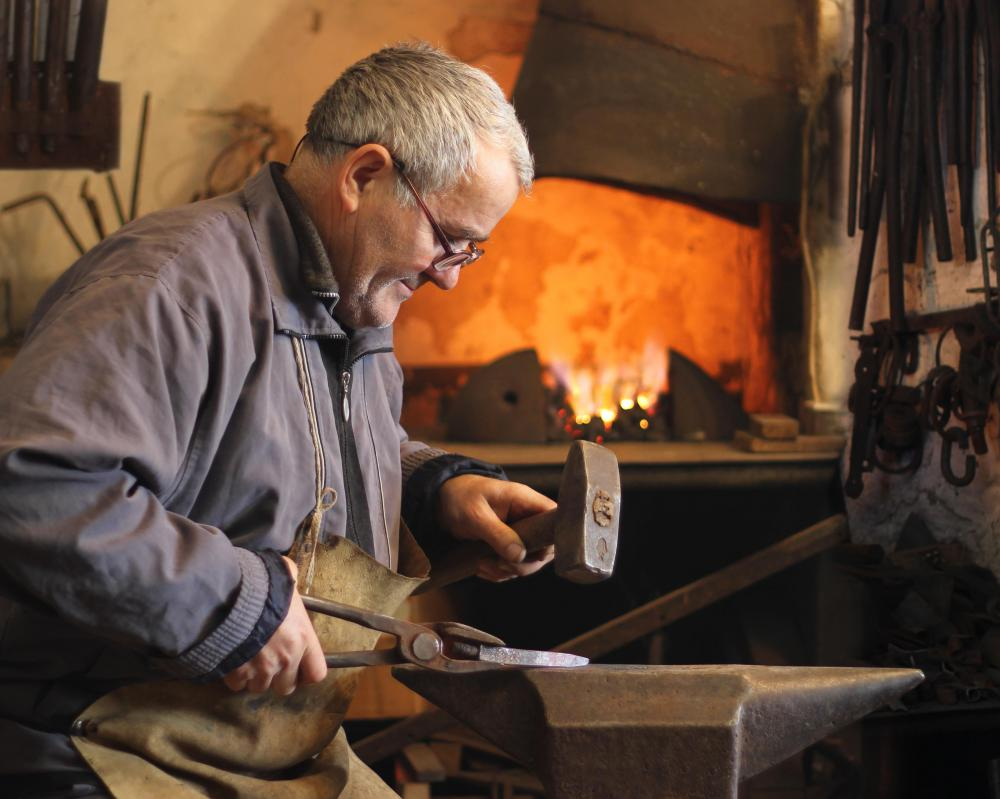 A blacksmith uses a hammer and other tools to form an iron rod into shape.