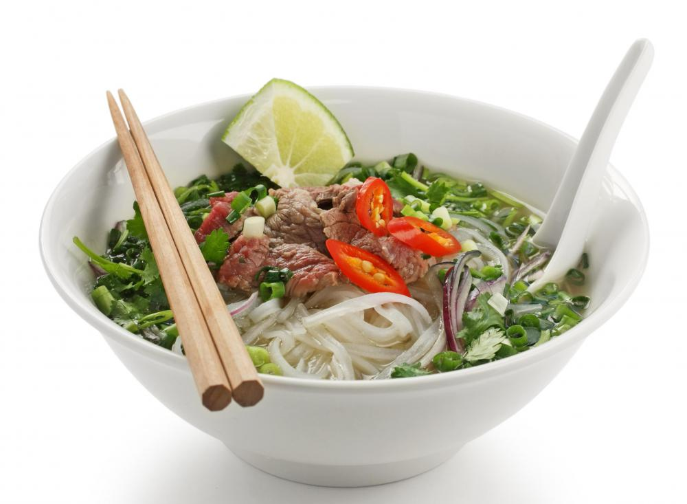 A bowl of pho, with a set of bamboo chopsticks.