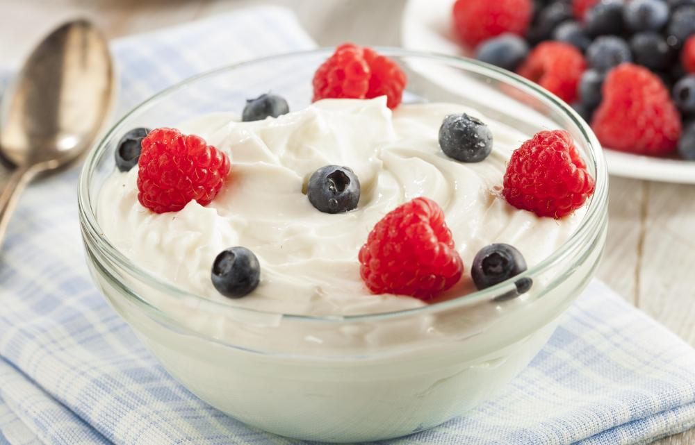 A bowl of thick Skyr yogurt garnished with blueberries and strawberries.