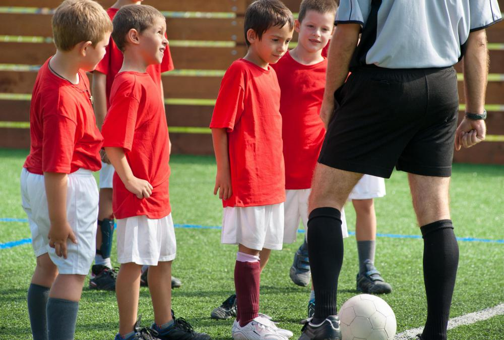 Coaches teach young soccer players the fundamentals of ball control.