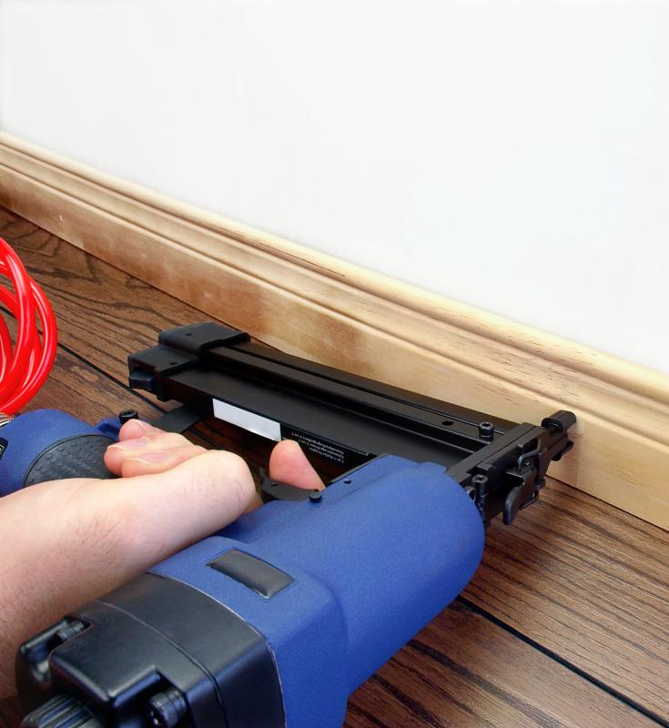 Nail gun being used to secure baseboard to a wall.