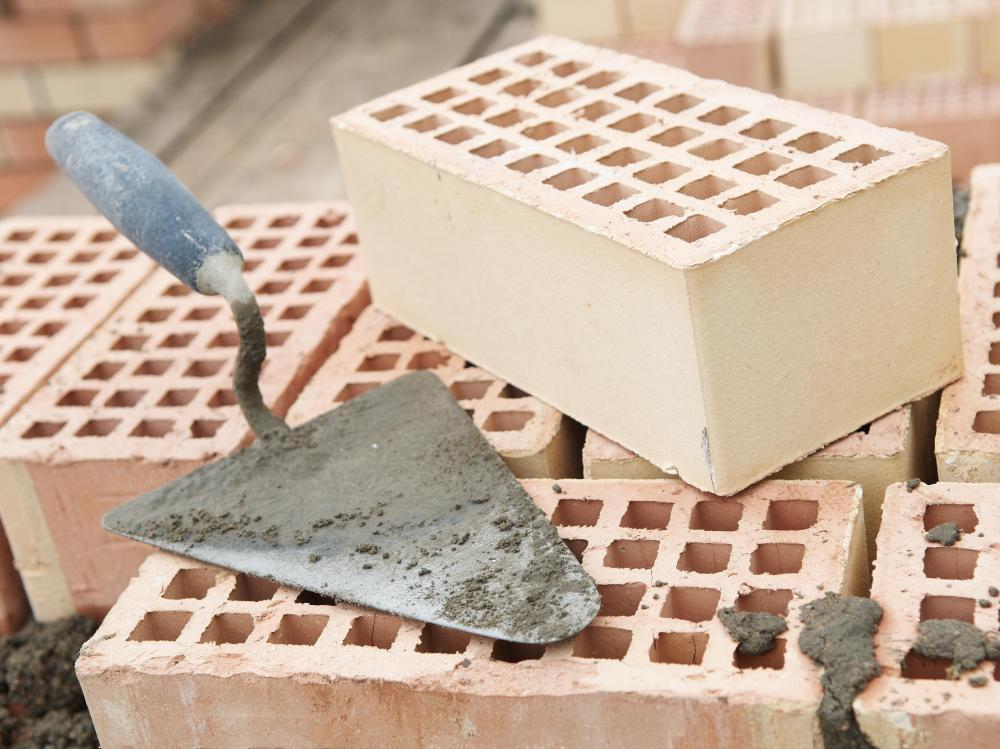 A brick trowel and recycled bricks.