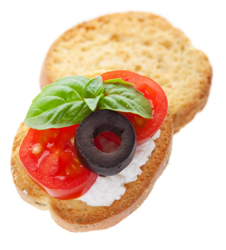 An hors d'oeuvre with cheese, tomato, olive and basil.