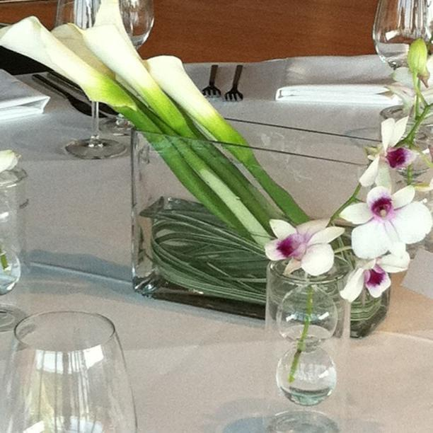 Tropical flowers like orchids and lilies in a glass vase make a great centerpiece.