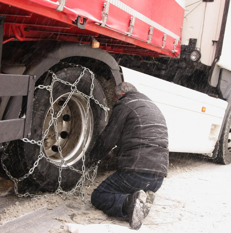 A truck driver may need to stop to change a tire or chain up the tires for winter weather.