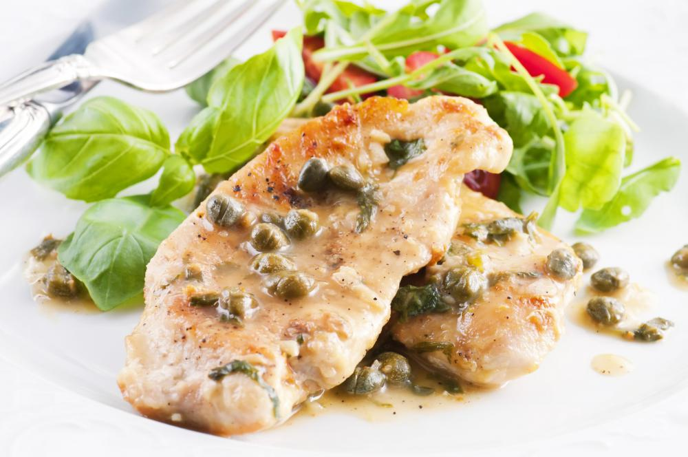 A photo of a plate of chicken piccata, likely prepared by a food stylist.