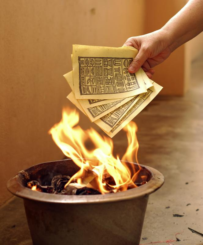 A person burning a facsimile of ancient Chinese money for a deceased person.