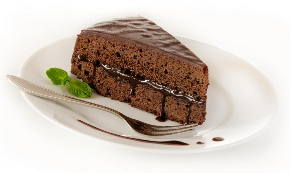 A slice of chocolate cake with icing in the middle.