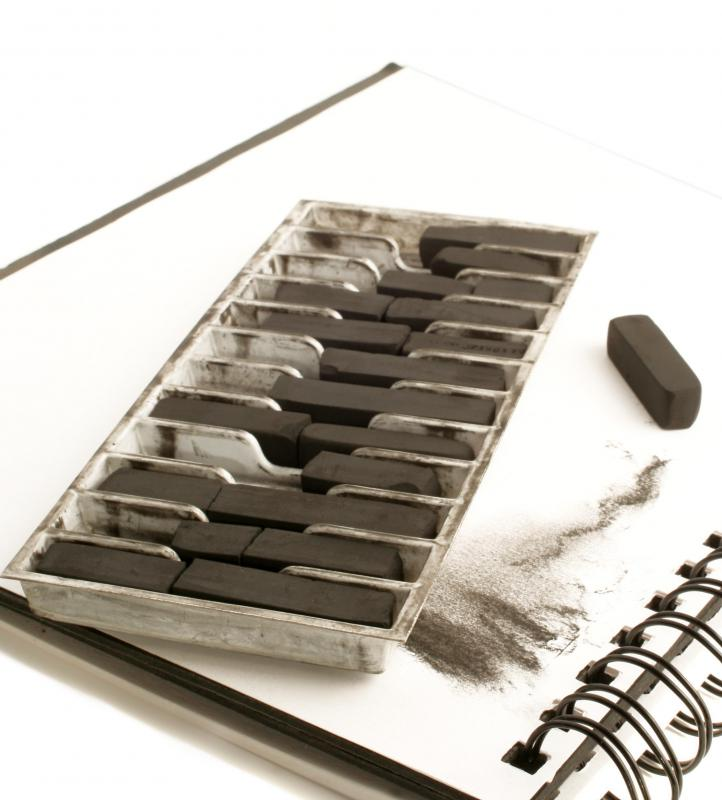 Compressed charcoal sticks may be used when creating a mixed media collage.