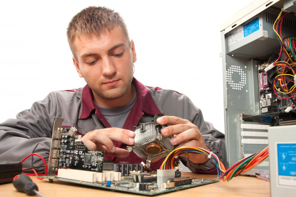A computer technician works on computer.