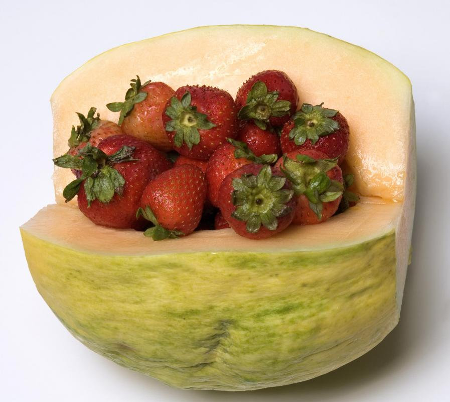 A cut crenshaw melon filled with strawberries included in a fruit basket.