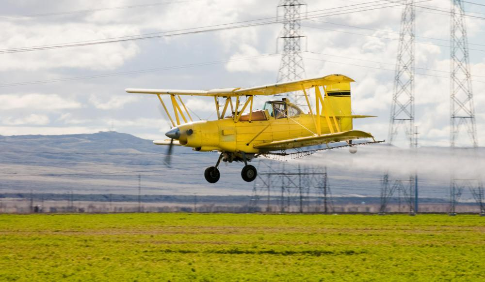 A crop duster sprays crops with pesticides or fertilizers.