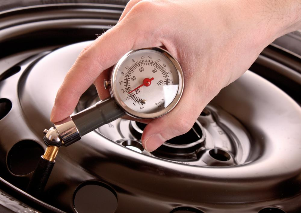 A man checks the air pressure in a car tire through the Schrader valve.