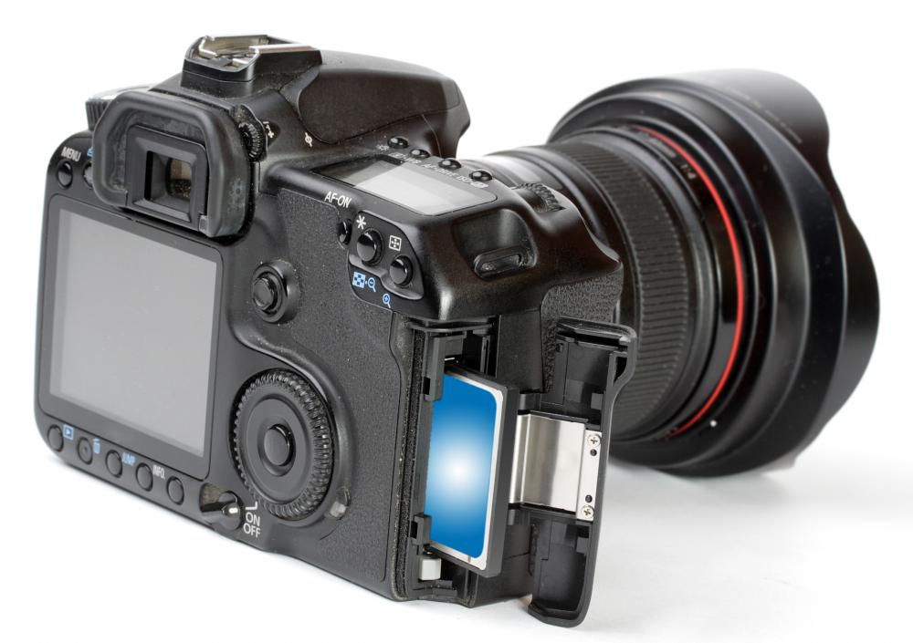 After taking photos with a digital camera, a photographer can transfer the images onto a computer for editing.
