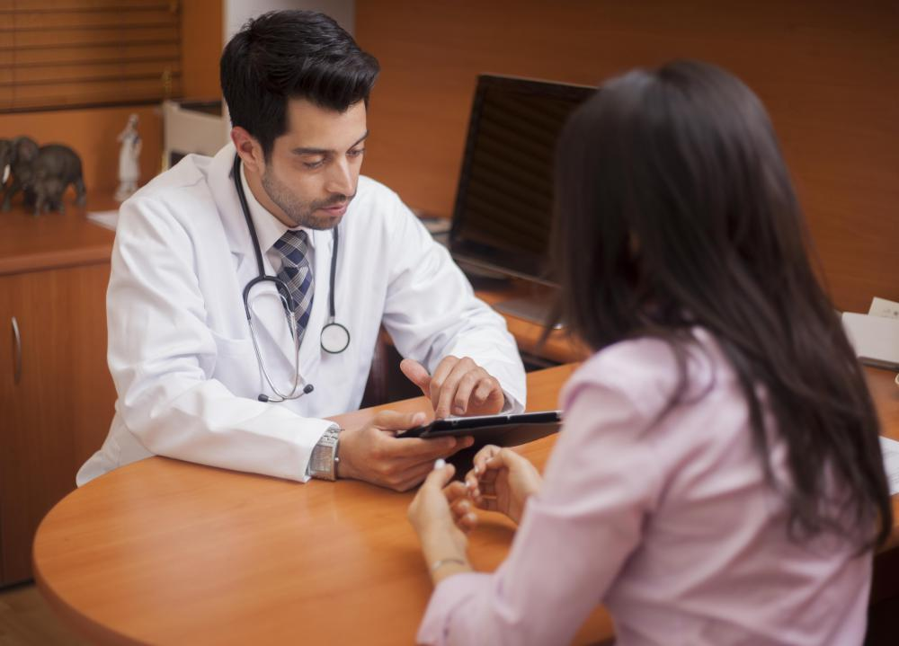 Medical office administrators may work with electronic health records filed by doctors on a tablet or computer.