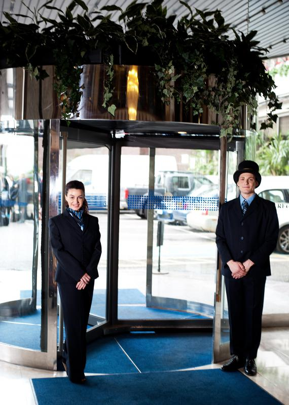 Bellhops, also called doormen, often help hotel patrons call cabs.