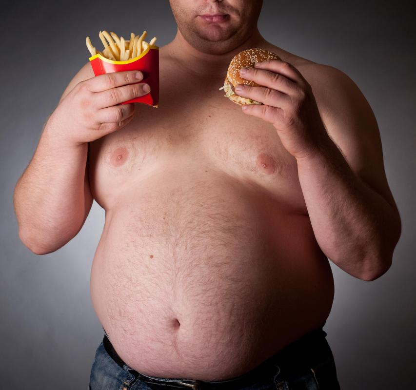 An overweight man with a fast food burger and fries.
