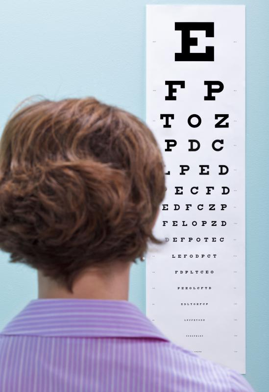 An eye surgeon uses charts with different sized letters and numbers to gauge a patient's vision.