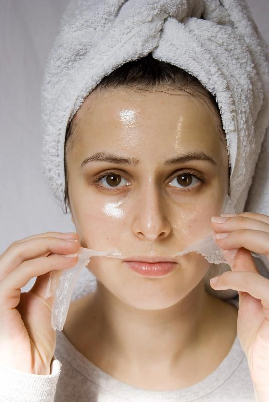 A woman removing a facial mask at a city spa.