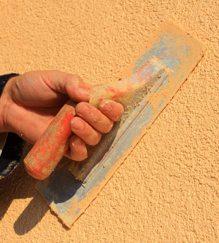 A person repairing stucco.