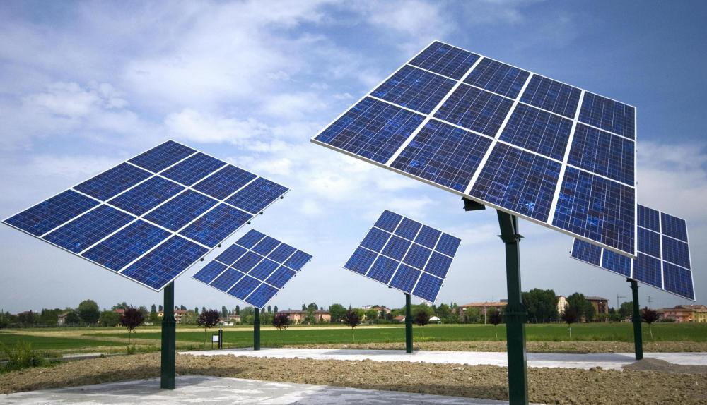 An array of solar panels is pointed at the sun to absorb solar energy.