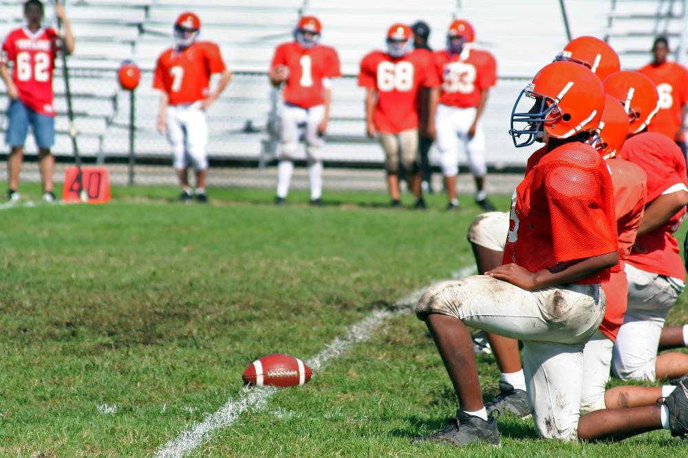 Football players kneel patiently on the sidelines during a drill.