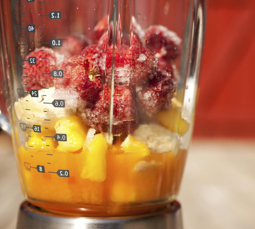Various types of fruit, yogurt, and ice are blended together in a smoothie maker.