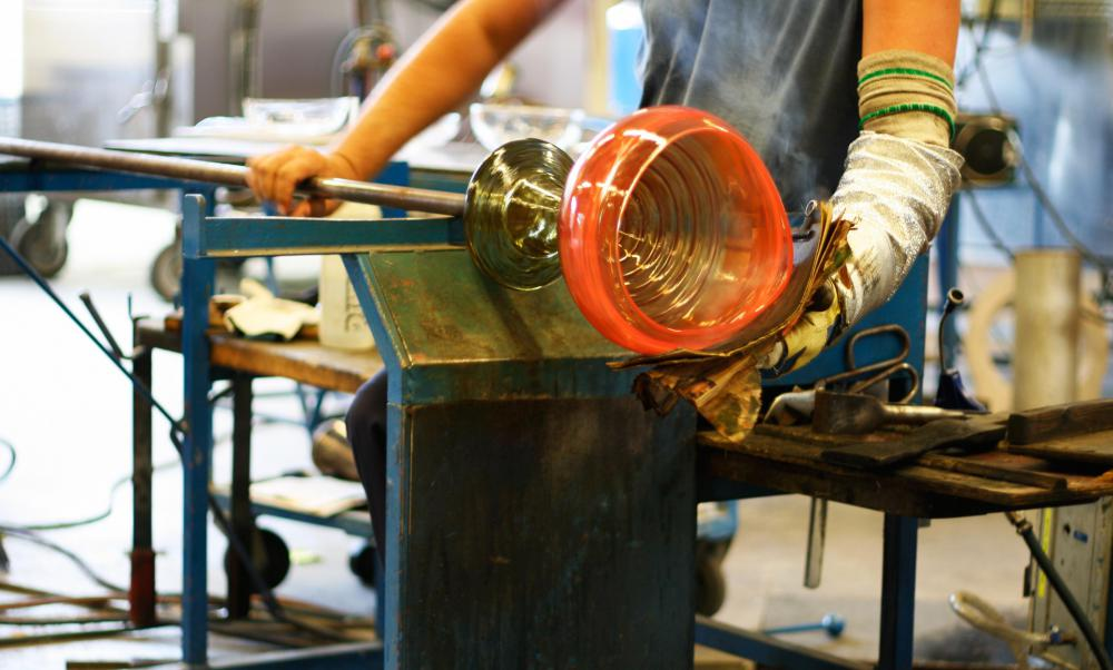 Many glass products are made in factory production lines, but some artisan glass blowers still use blowpipes to inflate and shape molten glass into items such as vases, bottles or cups.