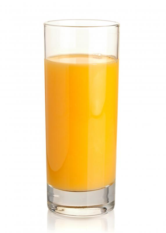 A glass of orange juice, which is used in making an orange banana smoothie.