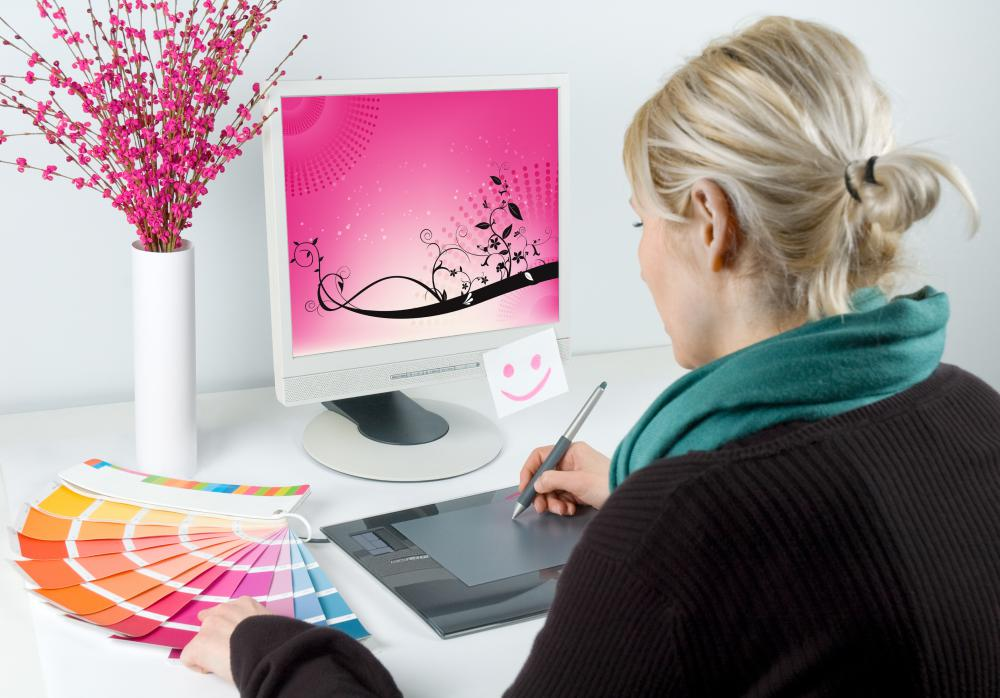 A graphic artist creates digital designs on a computer.