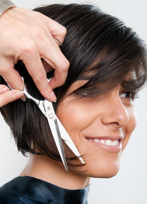 A hairstylist cutting a graduated bob with long bangs.