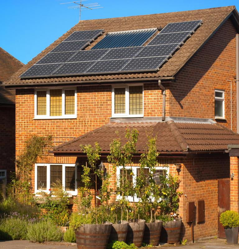 Eco home builders use photovoltaic roof panels and other sustainable materials in building.