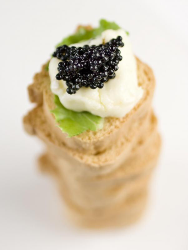 Caviar on melba toast with crème fraîche and basil.