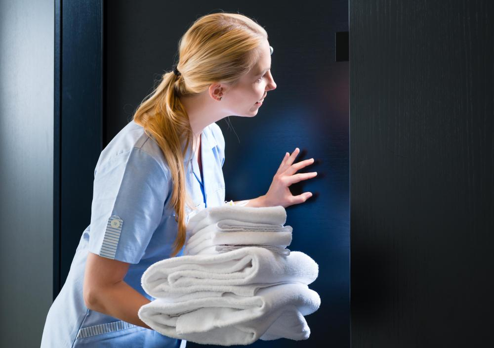 A housekeeping supervisor ensures rooms are cleaned effectively by staff members.