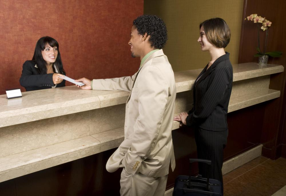 A front desk agent checks in guests.