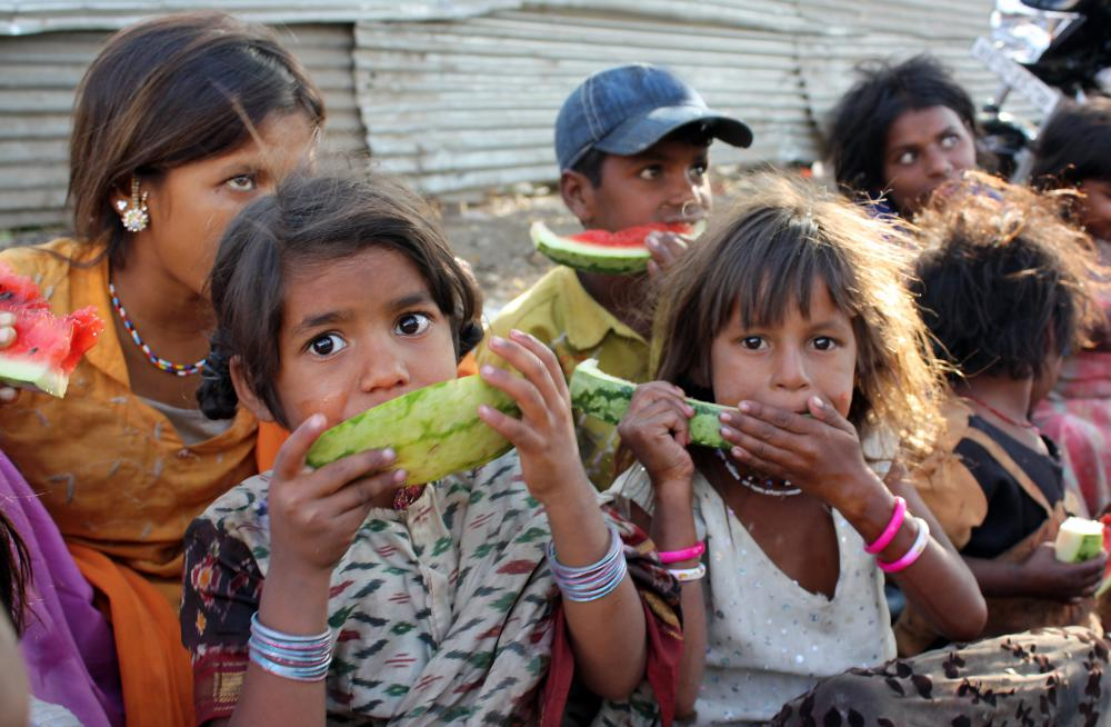 Impoverished children eating watermelon.