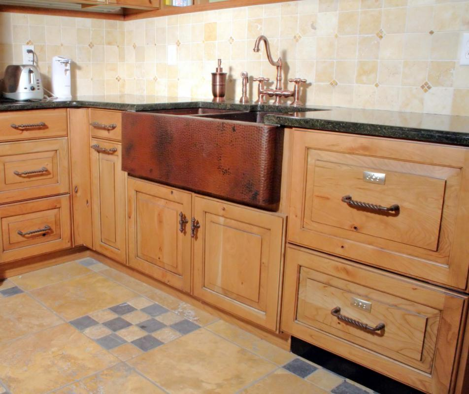 a kitchen with a tile backsplash behind the sink and countertops