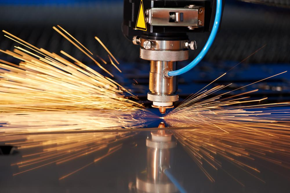 A carbon dioxide laser cutter is used to cut a sheet of metal.