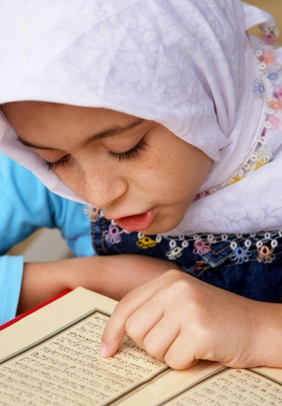 A young Muslim girl reading the Qur'an.