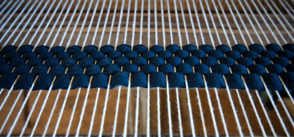 A loom helps crafters weave yarn into patterns.