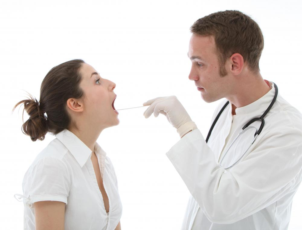A doctor checking the tonsils.