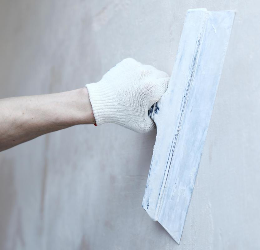 A maintenance person applies a skim coating to a wall after repairing a crack.